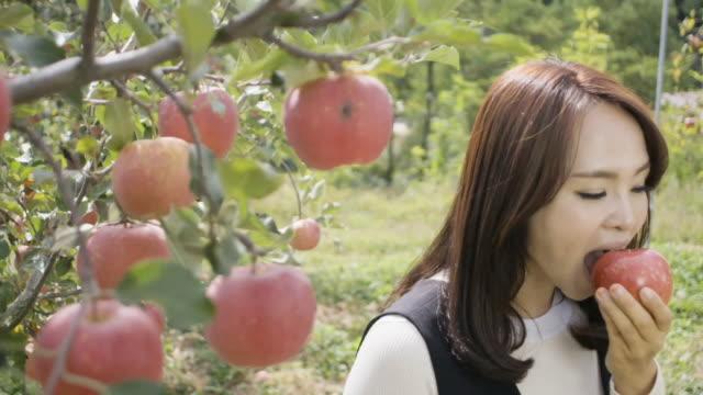 Woman Eating apple in farm