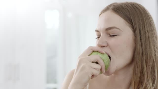 vidéos et rushes de femme mangeant une pomme - pomme