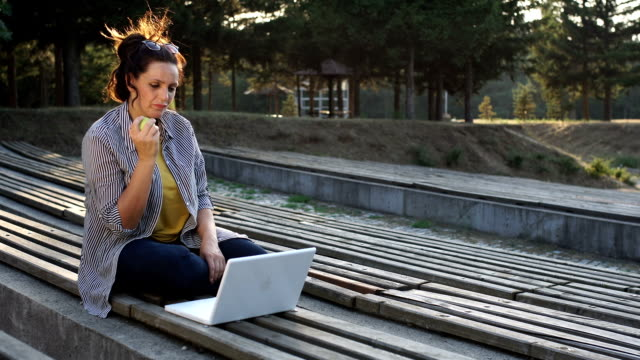 Woman eating apple while working
