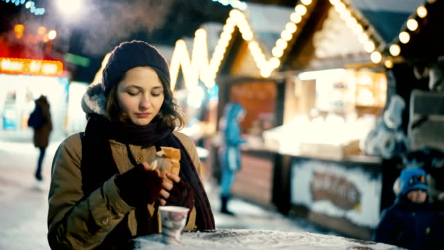 woman eating bakery and drinking hot wine  on christmas market - bancarella video stock e b–roll
