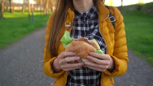 woman eating burger and walking - sandwich stock videos & royalty-free footage