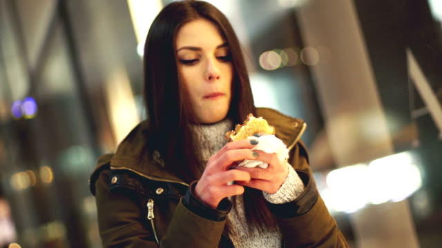 woman eating burger at the street - long hair stock videos & royalty-free footage