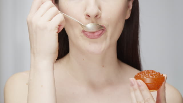 woman eating caviar with a silver spoon enjoying the taste indoors shot on red epic - spoon stock videos & royalty-free footage