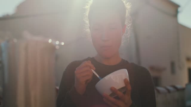 woman eating cereal in sunshine - frühstück stock-videos und b-roll-filmmaterial