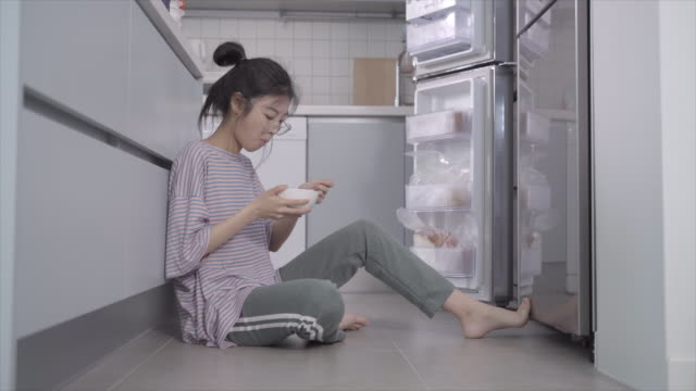 vídeos y material grabado en eventos de stock de woman eating cereal next to an open fridge door, seoul, south korea - recostarse
