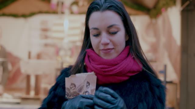 stockvideo's en b-roll-footage met woman eating chestnuts at christmas market - noot