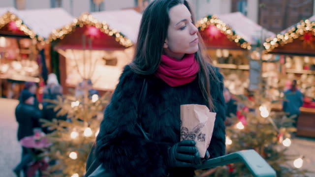 woman eating chestnuts at christmas market - nut food stock videos & royalty-free footage
