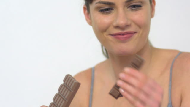 cu tu slo mo woman eating chocolate / london, greater london, united kingdom - haar nach hinten stock-videos und b-roll-filmmaterial