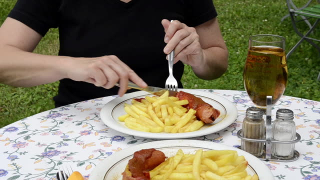 ms woman eating curry sausage and french fries / mainburg, bavaria, germany - fettgebraten stock-videos und b-roll-filmmaterial