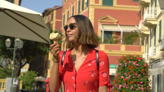 a woman eating gelato ice cream while traveling in a luxury resort town in italy, europe. - slow motion - gelato stock videos and b-roll footage