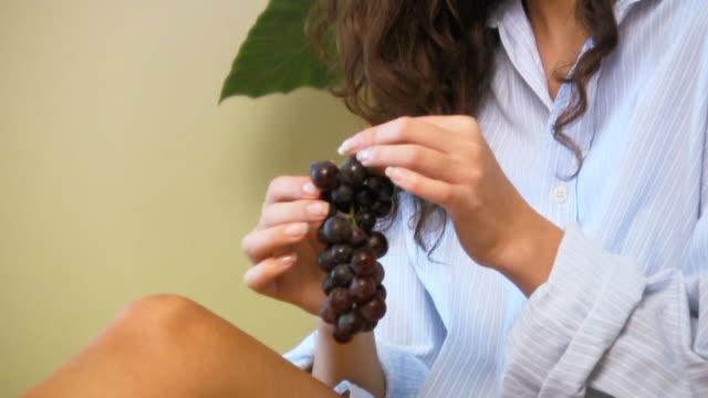 vidéos et rushes de femme manger le raisin - raisin noir