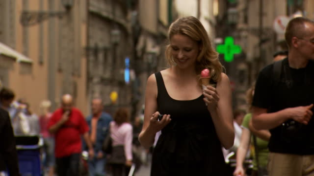 a woman eating ice cream answering her cellular phone - see other clips from this shoot 1150 stock videos & royalty-free footage
