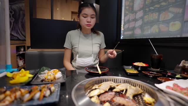 vídeos de stock e filmes b-roll de woman eating japanese style grilled food at a restaurant. - escolher