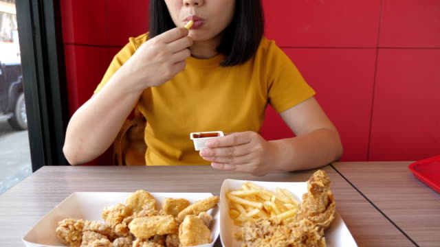 vídeos de stock e filmes b-roll de woman eating junk food french fries and fried chicken with ketchup - sódio