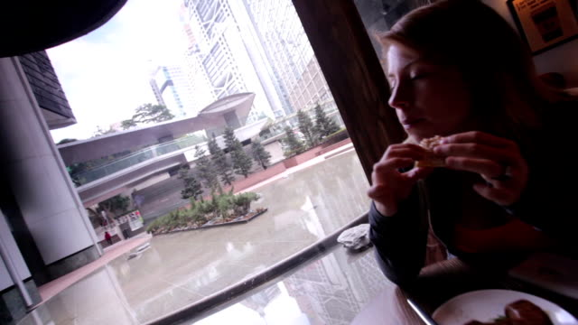 woman eating lunch in a city cafe - bagel stock videos & royalty-free footage