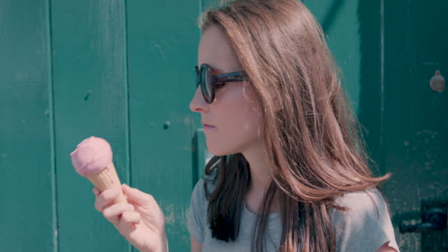 woman eating pink ice cream - lecken stock-videos und b-roll-filmmaterial
