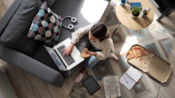 Woman eating pizza and working on laptop at home