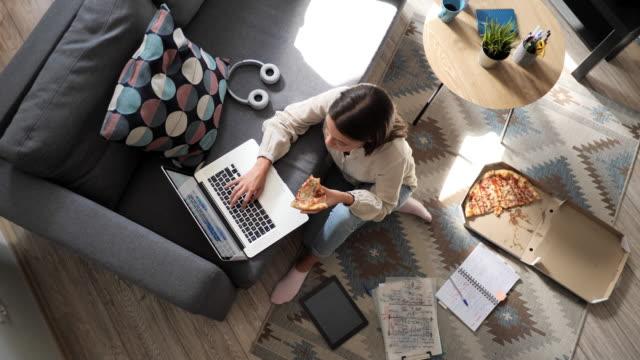 ピザを食べて、自宅でラップトップに取り組んでいる女性 - ズーム点の映像素材/bロール