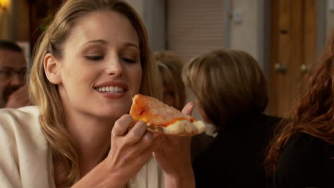 a woman eating pizza outdoors at a restaurant - see other clips from this shoot 1150 stock videos & royalty-free footage