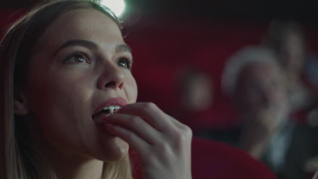 woman eating popcorn in cinema - cinema stock videos & royalty-free footage