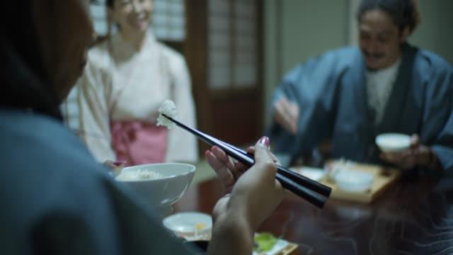 vídeos de stock, filmes e b-roll de mulher que come o arroz com os chopsticks no ryokan japonês tradicional - washitsu