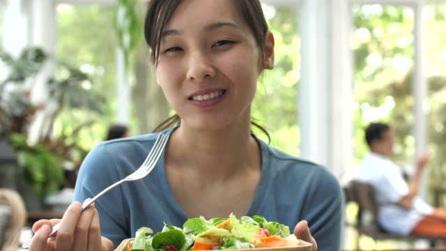 Woman Eating Salad and Smiling looking at camera