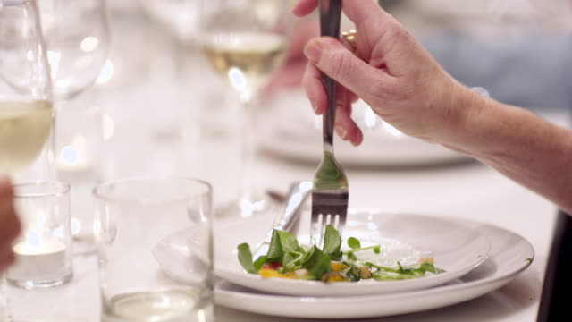 vídeos y material grabado en eventos de stock de ms cu woman eating salad during dinner party with friends - ensalada