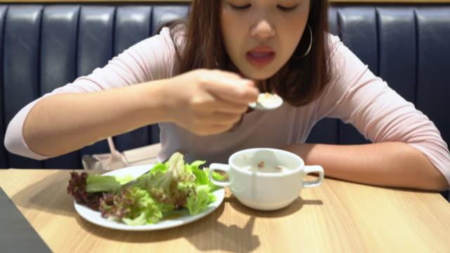vídeos y material grabado en eventos de stock de mujer comiendo comida vegana ensalada - sólo una adolescente
