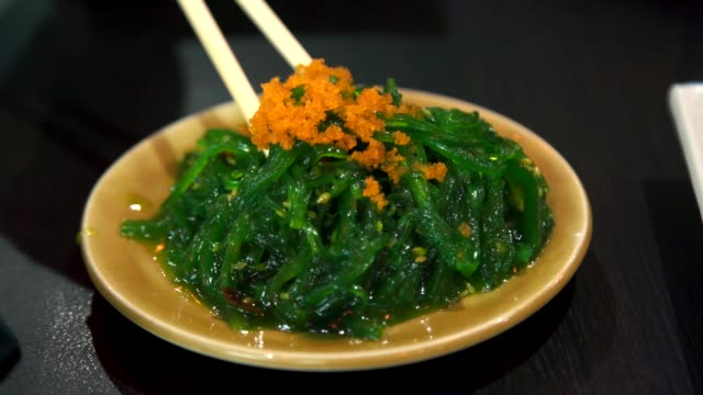 Woman Eating Seaweed Salad with Shrimp Eggs in Japanese Food.
