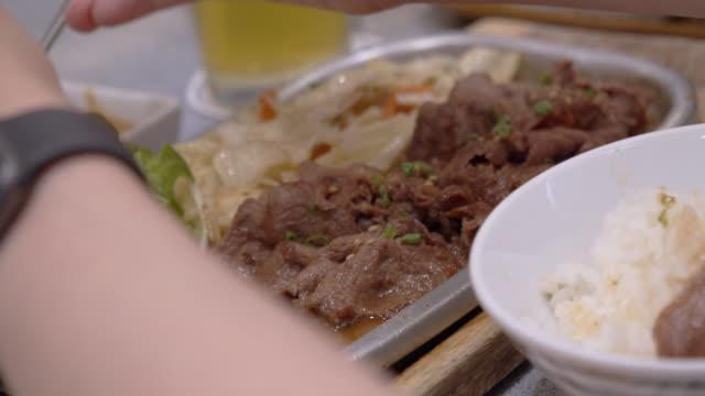 vídeos de stock, filmes e b-roll de mulher comendo fatias de carne em um prato quente. yakiniku - comida japonesa