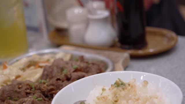 woman eating sliced meat on a hot plate. yakiniku
