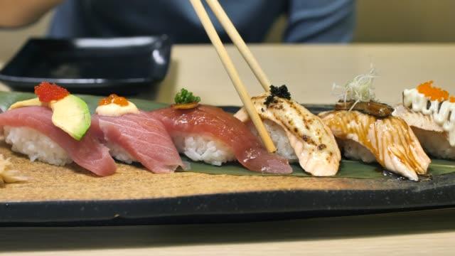 vídeos de stock e filmes b-roll de woman eating sushi in japan restaurant - sashimi
