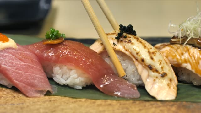 woman eating sushi in japan restaurant - japanese food stock videos & royalty-free footage