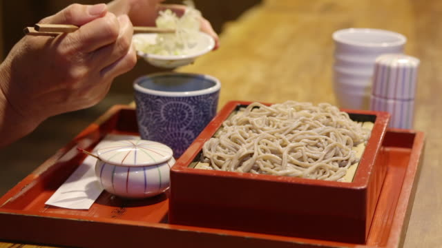Woman eating traditional soba noodles