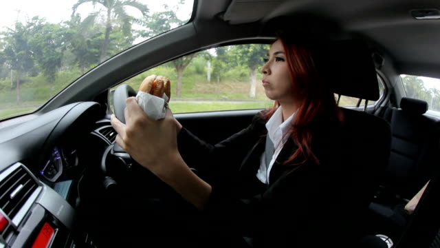 woman eating while driving to work - driver occupation stock videos & royalty-free footage