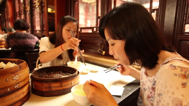 Woman eating Xiaolongbao in restaurant