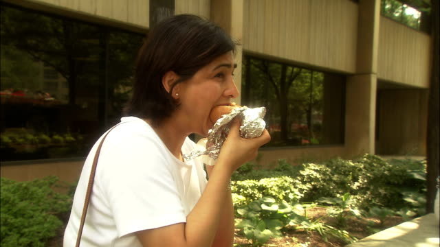 a woman eats a hot dog out of a foil wrapper. - unhealthy eating stock videos & royalty-free footage