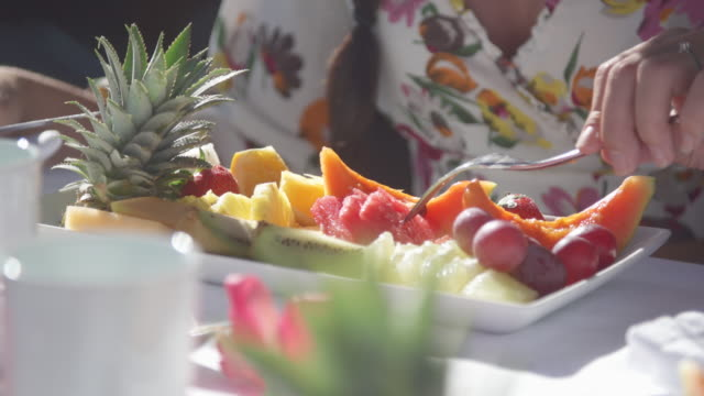 A woman eats fresh fruit at a tropical island resort.
