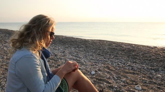 vidéos et rushes de woman eats pomegranate on empty beach - solitude