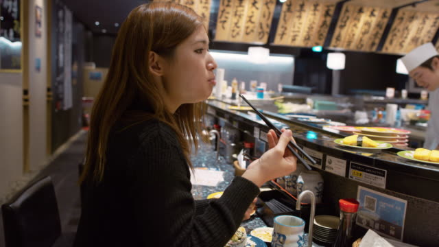 MS A woman eats sushi in a restaurant / Tokyo, Japan