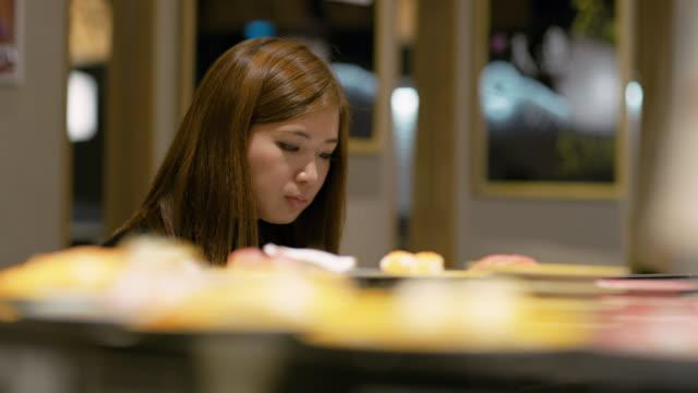 vídeos de stock e filmes b-roll de ls a woman eats sushi in a restaurant / tokyo, japan - sushi