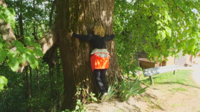 女性は木の幹を抱きしめる - 東ヨーロッパ民族点の映像素材/bロール