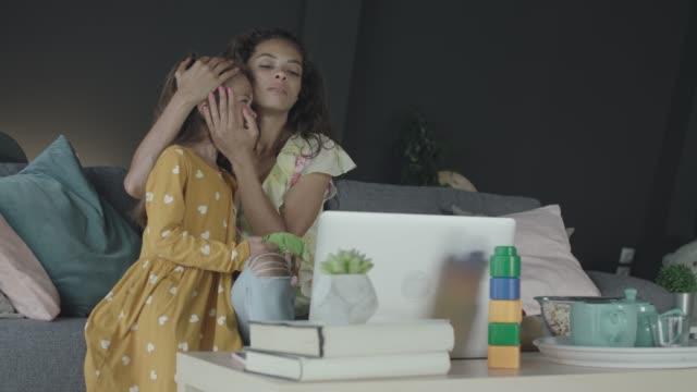 vídeos de stock, filmes e b-roll de mulher abraçando sua filha enquanto trabalhava em casa - mil tarefas