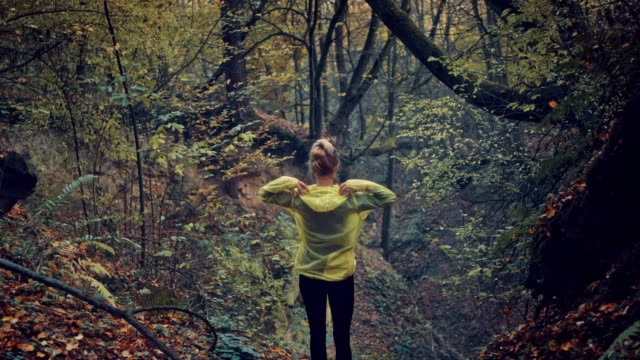 Woman embracing nature. Rainy, autumnal forest