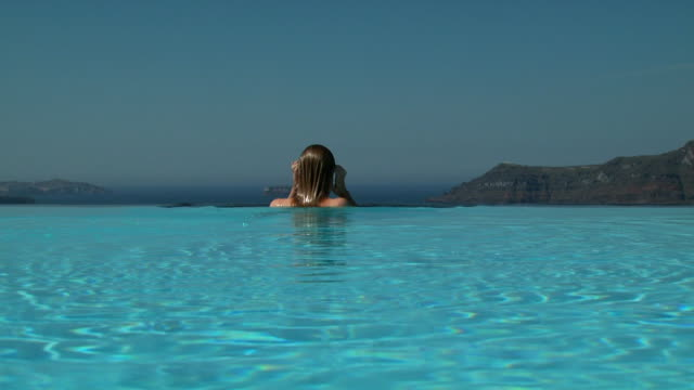 A woman emerging from an infinity pool