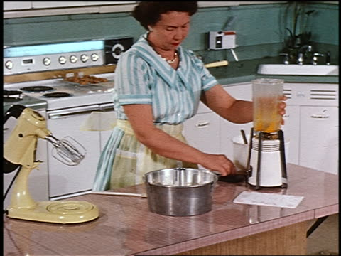 1958 woman emptying blender into pot on counter in kitchen