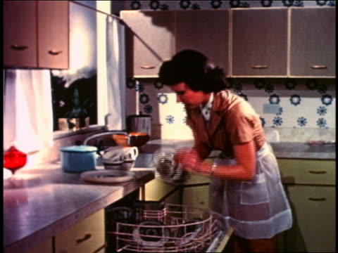 1958 woman emptying dishes from dishwasher in kitchen - lavastoviglie video stock e b–roll
