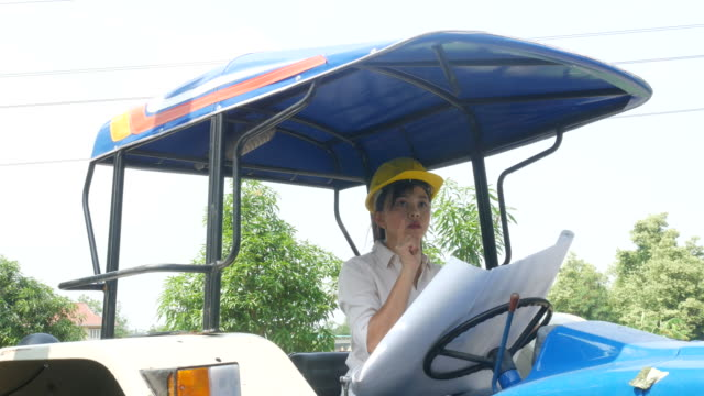 vídeos de stock e filmes b-roll de woman engineer checking blueprint on tractor car - engenheiro civil