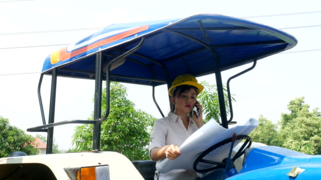 woman engineer using phone on tractor car - mechanical digger stock videos & royalty-free footage