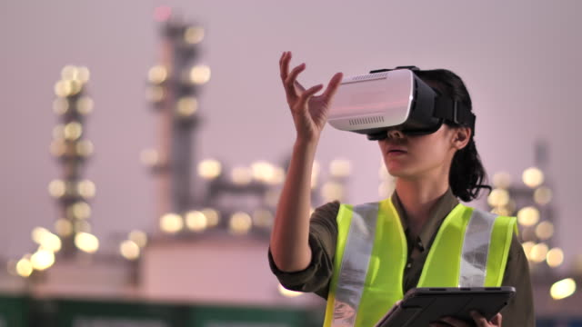 vídeos de stock e filmes b-roll de woman engineer wearing virtual reality headset in oil industrial plant at night - engenheiro